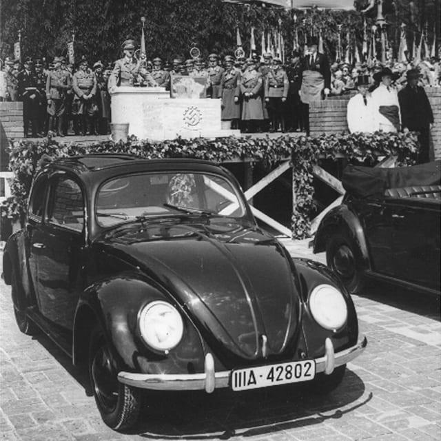 Adolf Hitler hält eine Rede. Vorne steht ein VW Käfer.