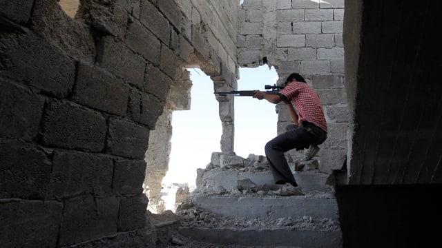 Ein Mann in rot-weiss gestreiftem Shirt schiesst mit einem Gewehr aus einem offensichtlich zerstörten Gebäude heraus auf einen unsichtbaren Gegner.