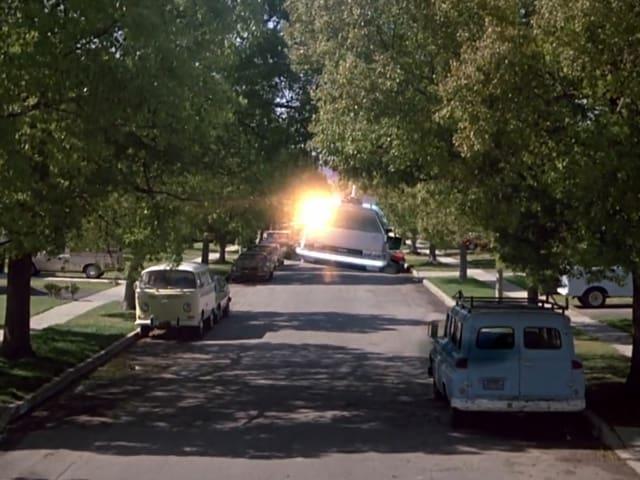 Ein Auto schwebt eine Strasse hinunter begleitet von einem Lichtblitz.