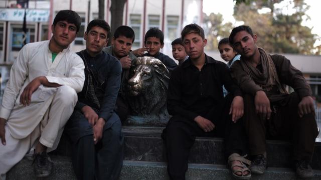 Junge Männer mit Bronzestatue eines Löwen.