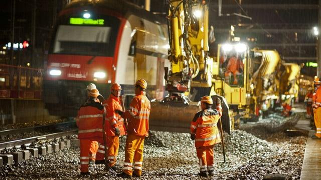 SBB-Zug fährt an Gleisbau-Arbeitern vorbei.