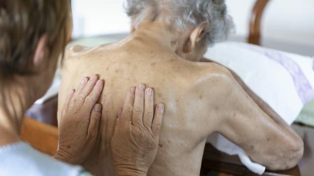 Eine Pflegefachkraft massiert einer Patientin den Rücken.
