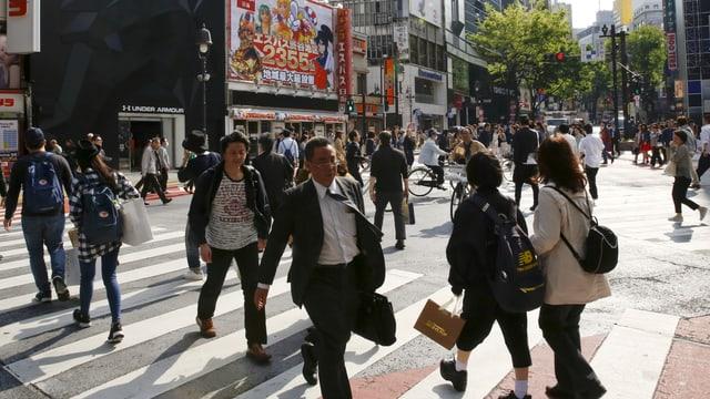 Menschen überqueren eine Strasse in Tokio.