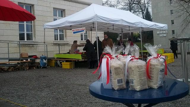 Auf einem Tischchen stehen Päckli mit Risotto. Im Hintergrund ein Festzelt mit Personen.