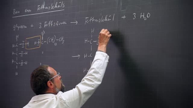 Mann in weissem Hemd schreibt mit Kreide auf eine Wandtafel.