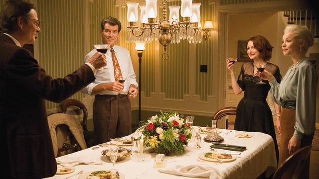 Zwei Männer und zwei Frauen stehen an einem elegant gedeckten Tisch und erheben die Gläser.