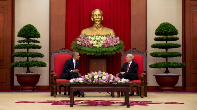Die beiden Politiker sitzen an einem mit Blumen geschmückten Tisch.