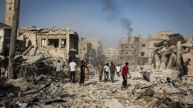Siria, ruinas da chasas suenter in'attatga, pliras persunas van tras las ruinas