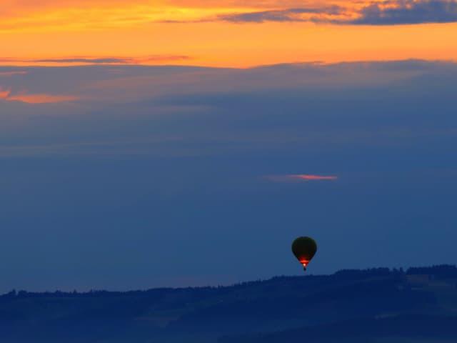 Ballon fliegt über der Landschaft. Es ist noch Dämmerung.