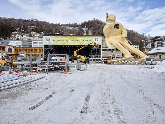 19 Meter hohe hölzerne Ski-Figur vor einer grossen Bühne in St. Moritz.