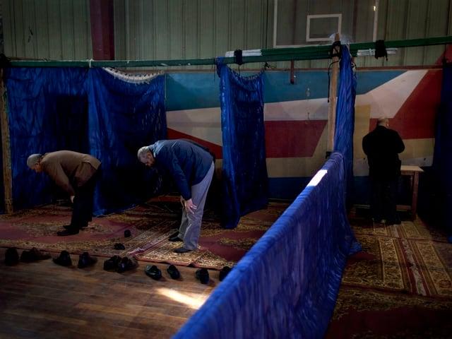 Wähler in einer Turnhalle.