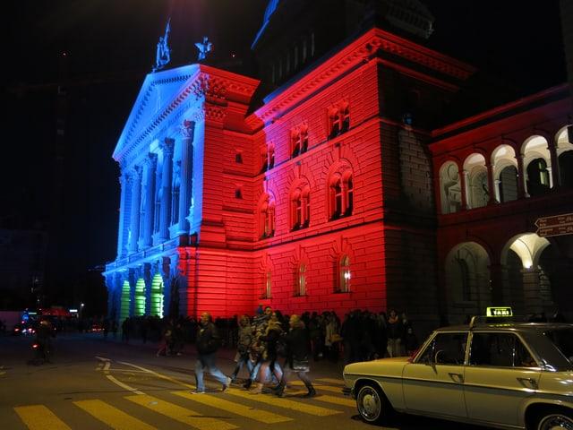 Oldtimer-Taxi vor dem rot-blau beleuchteten Bundeshaus