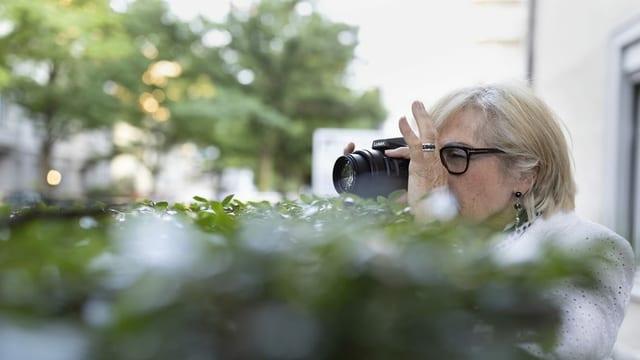 Frau mit Fotoapparat versteckt sich hinter einem Gebüsch