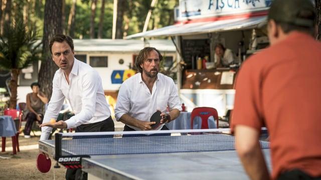 Zwei Männer stehen am Campingtisch, einer macht sich bereit zum Aufschlag.