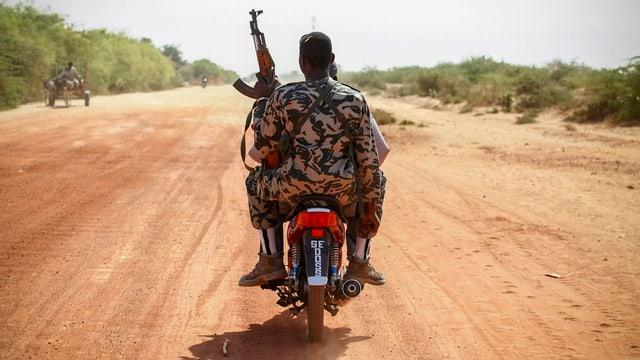 Ein malischer Soldat mit Maschinengewehr sitzt hinten auf einem Mofa. Staubige Strasse.