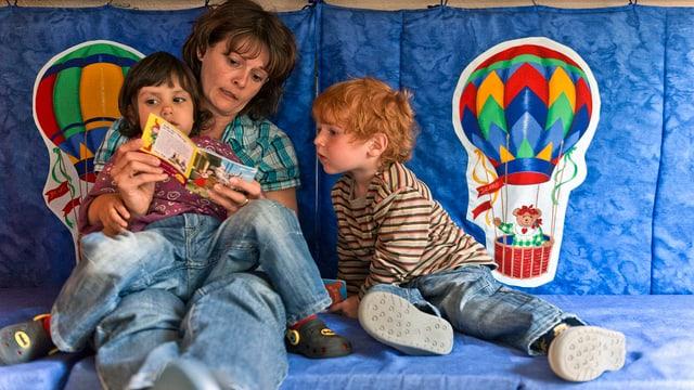 Eine Tagesmutter liest zwei Kindern aus einem Büchlein vor.