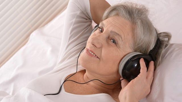 Eine ältere Frau mit Kopfhörern über den Ohren liegt in einem weiss bezogenen Bett.