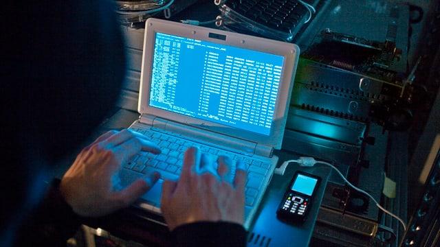 Ein Mann mit Kapuze tippt Befehle in seinen Laptop.