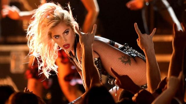 Sängerin auf der Bühne, umringt von jubelnden Fans.