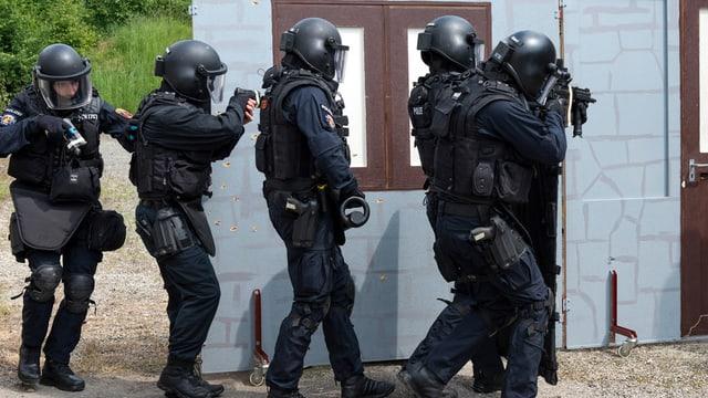 Schwarzgekleidete Polizisten mit Pistolen und Gewehren.