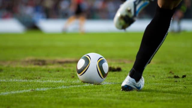 Beine eines Fussballspielers, der dabei ist, den Ball zu spielen.