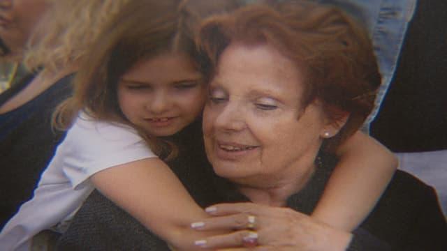 Ein Kind umarmt eine ältere Dame.