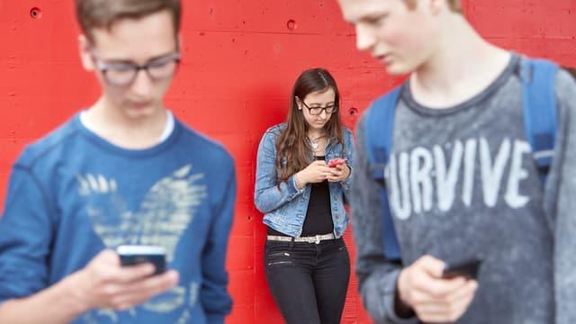 Jugendliche starren auf ihr Smatphone.