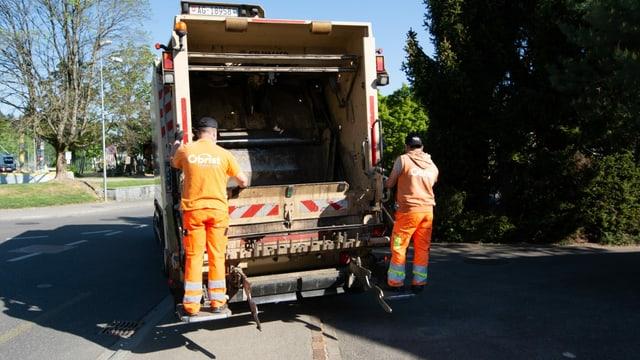 Zwei Müllmänner stehen auf der Plattform der Kehrichtabfuhr