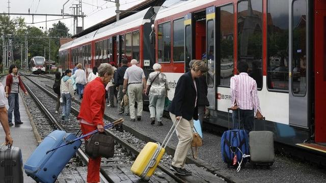 Passagiere steigen in einen Zug ein.