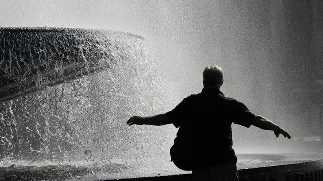Ein Mann steht vor einem Brunnen in der Sonne.