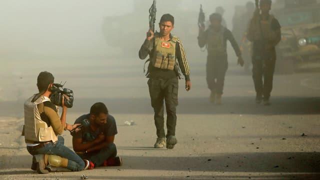 Ein Journalist kniet mit der Kamera neben einem verletzten Mann. Mehrere schwer bewaffnete Männer gehen an ihnen vorüber.