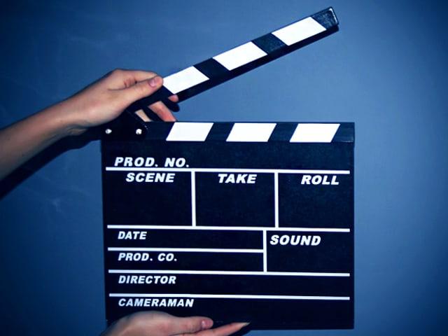 Eine weibliche Hand hält eine klassische schwarze Filmklappe vor blauem Hintergrund.