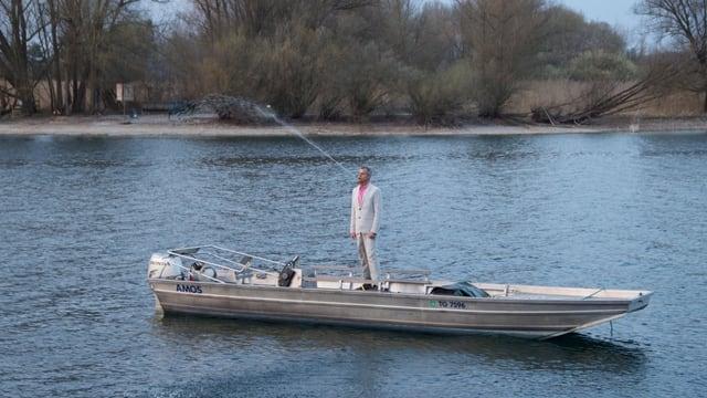 Mann in Boot stehend spuckt Wasser im hohen Bogen