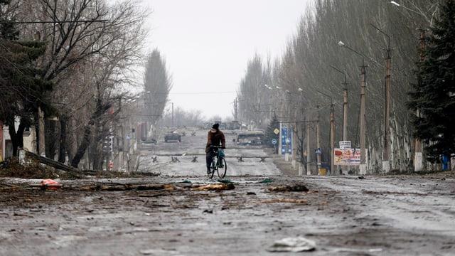 Mann mit einem Velo auf einer verwüsteten Strasse.