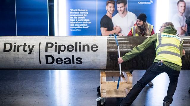 Zwei Greenpeace-Aktivisten rollen eine Pipeline ins Foyer des Hallenstadions
