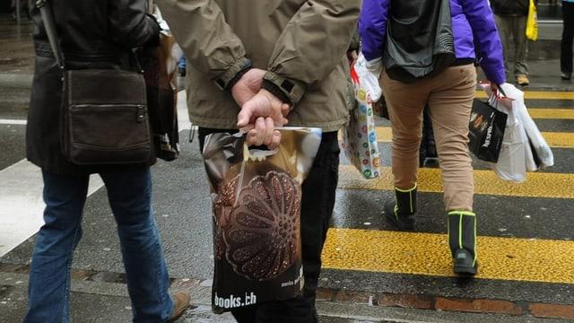 Menschen mit Einkaufstüten laufen über einen Fussgängerstreifen.