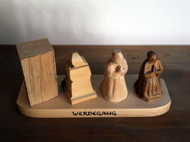 Das Bild zeigt den Prozess von einem Stück Holz in vier Schritten, wie es die Form einer Figur annimmt.
