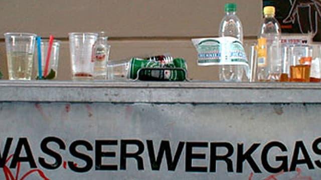 Abfallcontaier mit der Aufschrift Wassergasse. Darauf stehen leere Petflaschen und Bierdosen und -bescher.