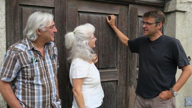 Drei Menschen stehen vor Holztüre.