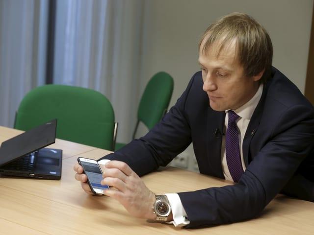 Taavi Kotka an einem Tisch mit Smartphone in der Hand.