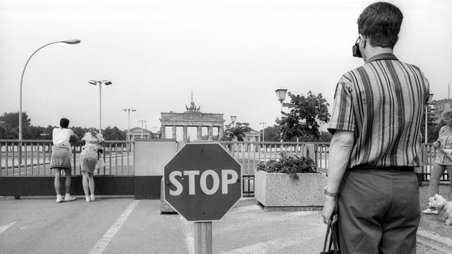 Passanten auf der Ostseite des Brandenburger Tors mit Stoppschild.