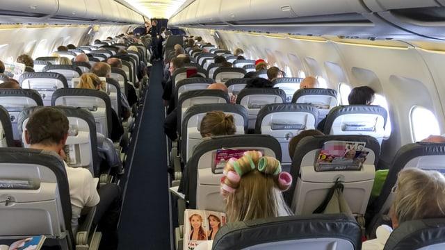 Symbolbild: Aufnahme der Flugzeugpassagiere von hinten nach vorn in einem Flugzeug.