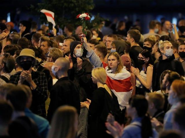 Eine Frau streckt inmitten von Demonstranten eine Hand voller Blumen in die Höhe, über die Schultern hat sie die Landesflagge von Weissrussland gehängt.