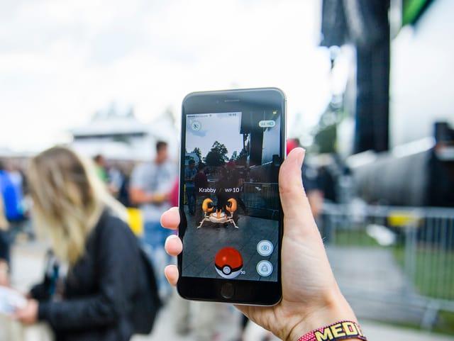 Vor Freilichtbühne hält eine Hand hält ein grosses Handy, auf dem ein Pokémon zu sehen ist.