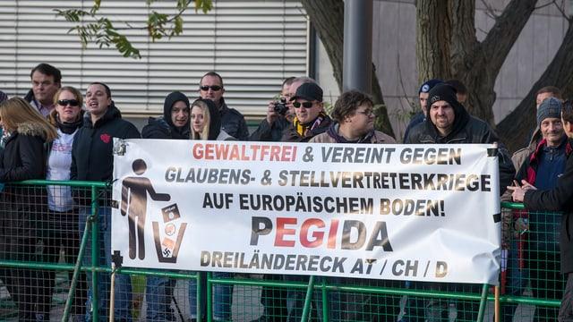 Pegidademonstration: Ein Transparent ist an einem zaun befestigt und dahinter steht eine Gruppe von Menschen.