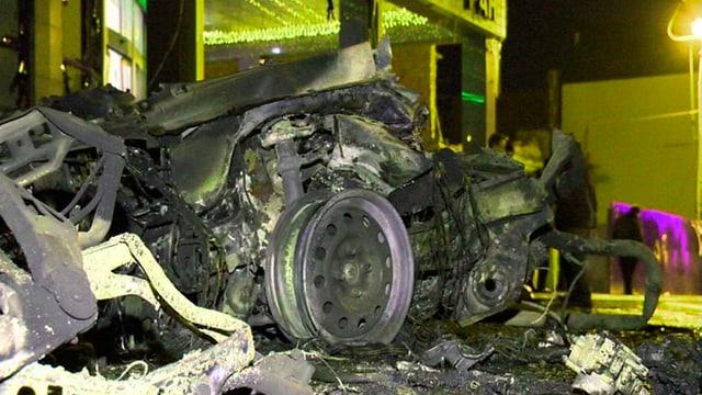 Autowrack vor einem zerstörten Gebäude.