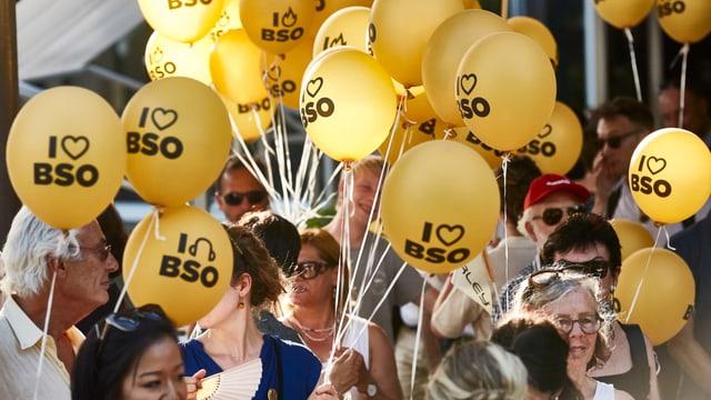 Menschen mit gelben I Love BSO Ballonen