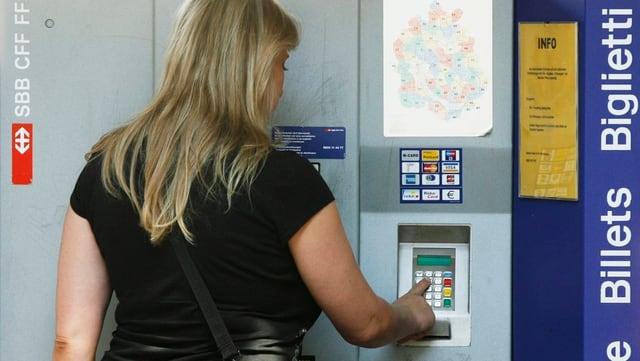 Eine Frau löst ein Billet an einem Automaten.
