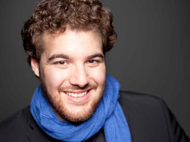 Der Sänger Mauro Peter lächelt und trägt einen Schal um den Hals.
