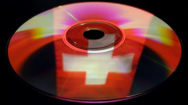 Symbolbild: CD mit Schweizer Flagge, die sich darin spiegelt.
